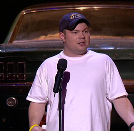 A standup comedian wearing a Kent State cap