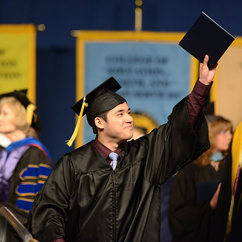Graduate with degree in hand, arm raised, cap and gown