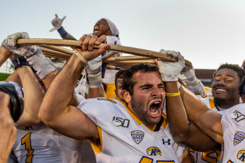 Members of the Kent State football team celebrate with the Wagon Wheel after defeating Akron 26-3.