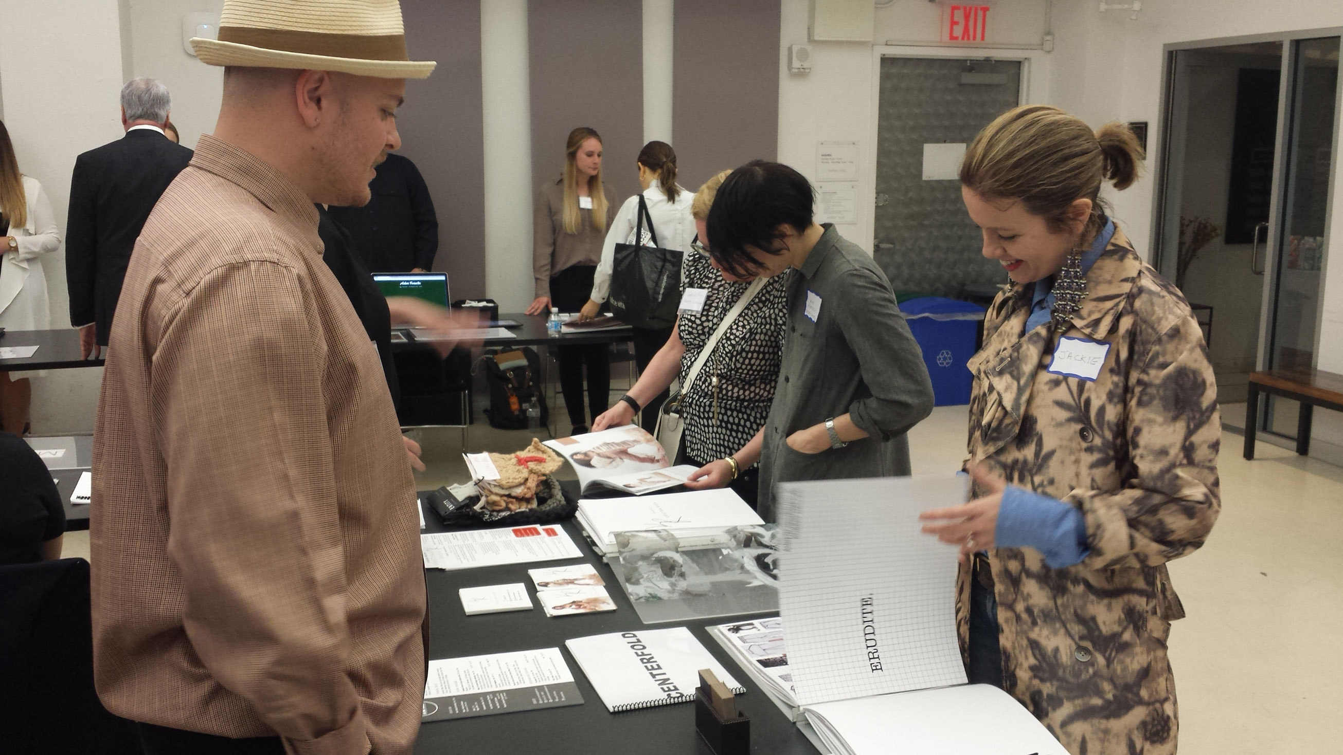 Student showing fashion design portfolio to industry professional during 2018 Portfolio Showcase