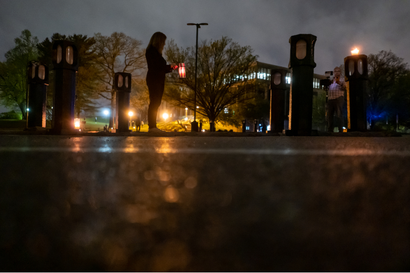 Silhouetted by candlelight, Chic Canfora pays tribute to all of the students killed or wounded on May 4, 1970.