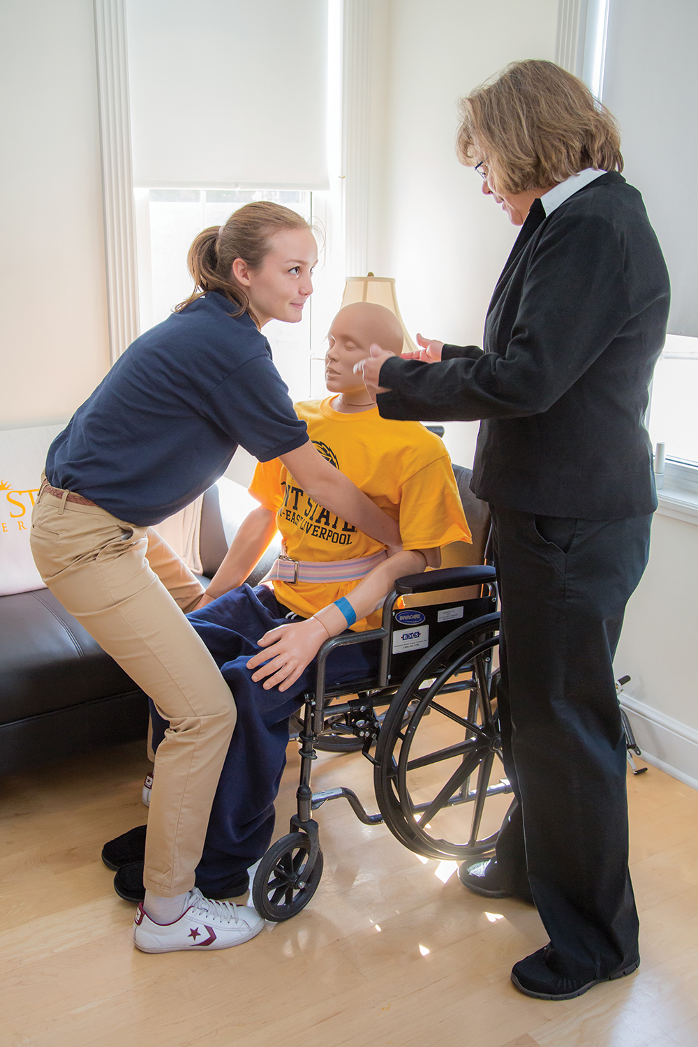 Associate lecturer Kathy Swoboda oversees a student practicing the transfer of a patient from a wheelchair to a couch.