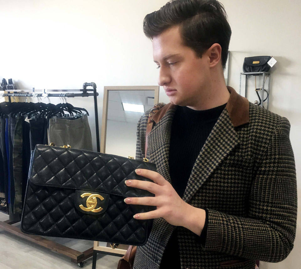 Morgan examines a classic Chanel flap bag at The Style Loop in Rocky River. (Photo courtesy Allison Carey/The Plain Dealer)