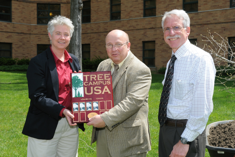 Heather White, Vice President Gregg Floyd and Tom Euclid accept Kent State's designation as an official Tree Campus, during an Arbor Day tree-planting ceremony beside Engleman Hall.