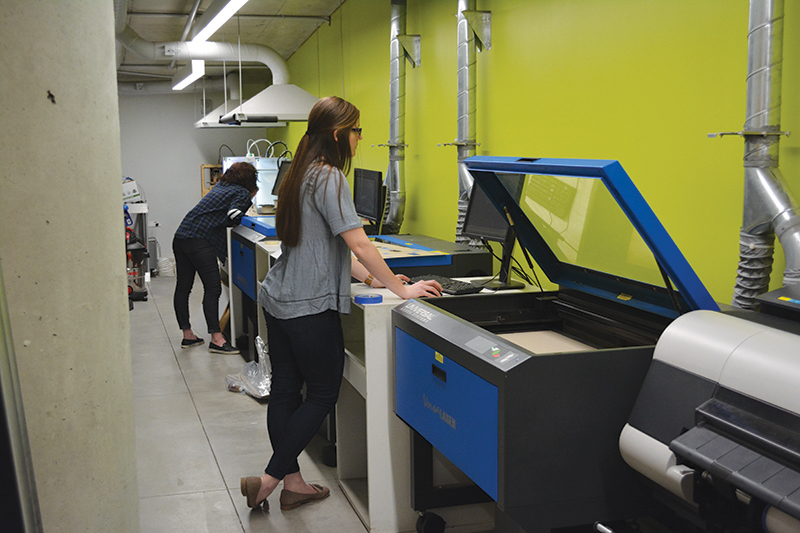 Female student using laser cutter