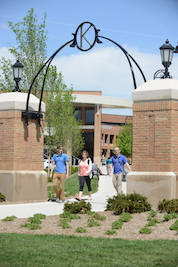 Kent State students walk to class through one of the gates on the Student Green.