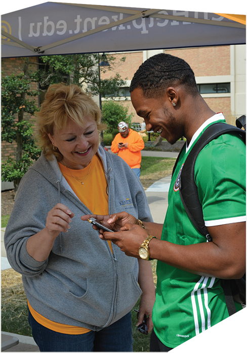 Tent volunteer helping a student with his phone during Welcome Weekend