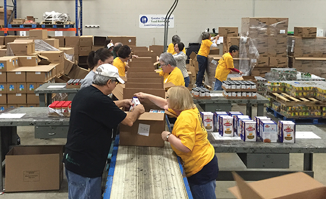 Kent State alumni and friends pack boxes of food at the Greater Cleveland Food Bank in 2016.