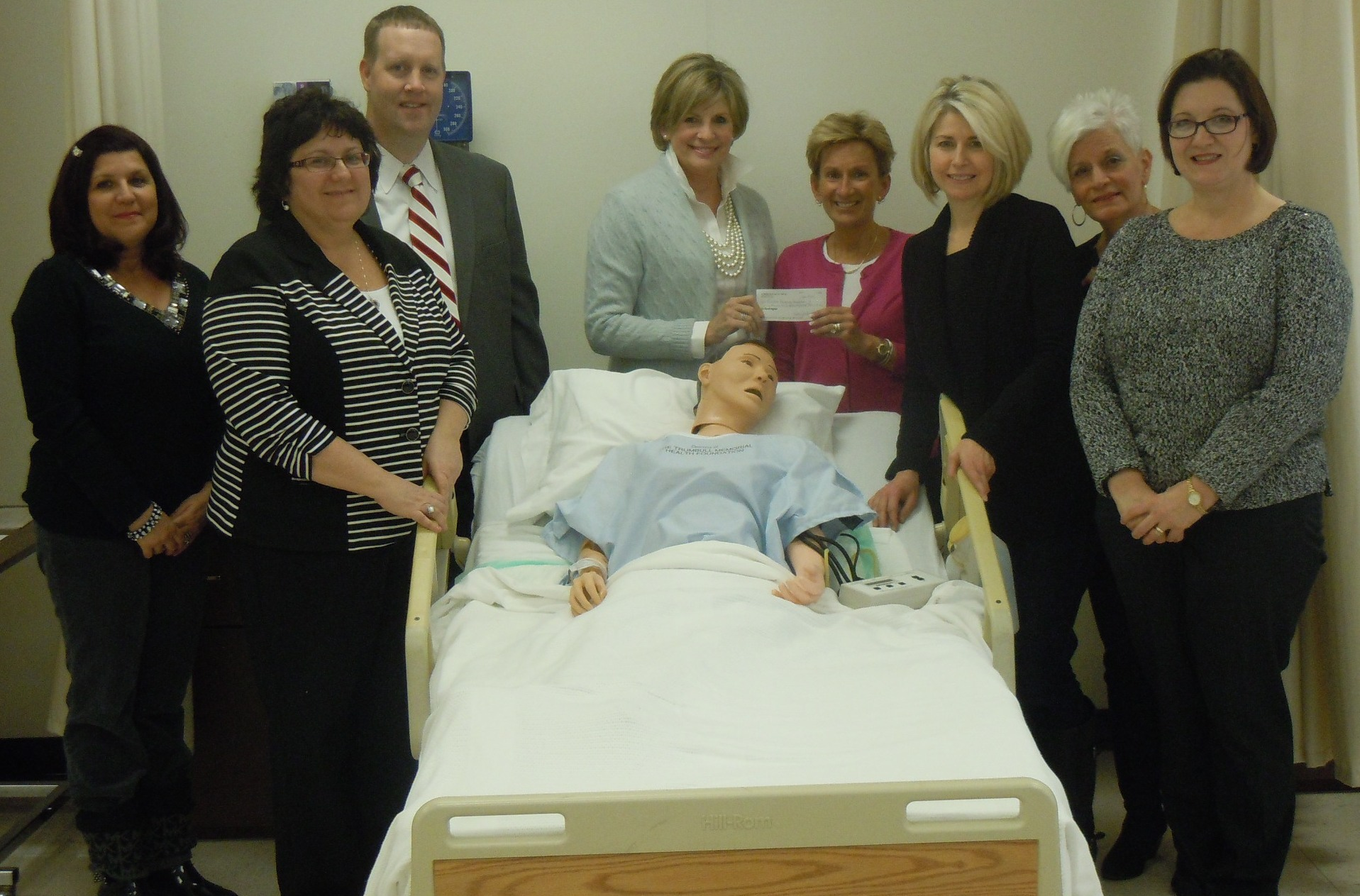 Sarah Vosmik (left center), president of the Women's Auxilary at Trumbull Memorial Hospital, presents a check of over $20,000 to Kathy Dwinnells (right center), Kent State University at Trumbull's nursing program coordinator.