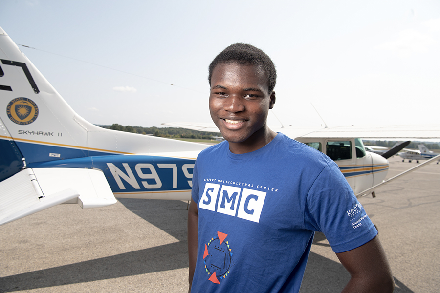 Divine Asante stands in front of a Kent State University airplane.