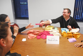 Pictured are participants playing the Game of Life, an interactive inequality simulation.