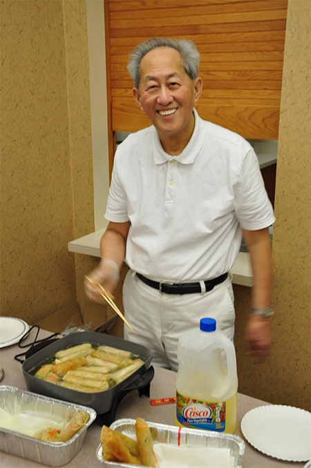 Dr. Bao Feng demonstrates how to make his spring rolls.