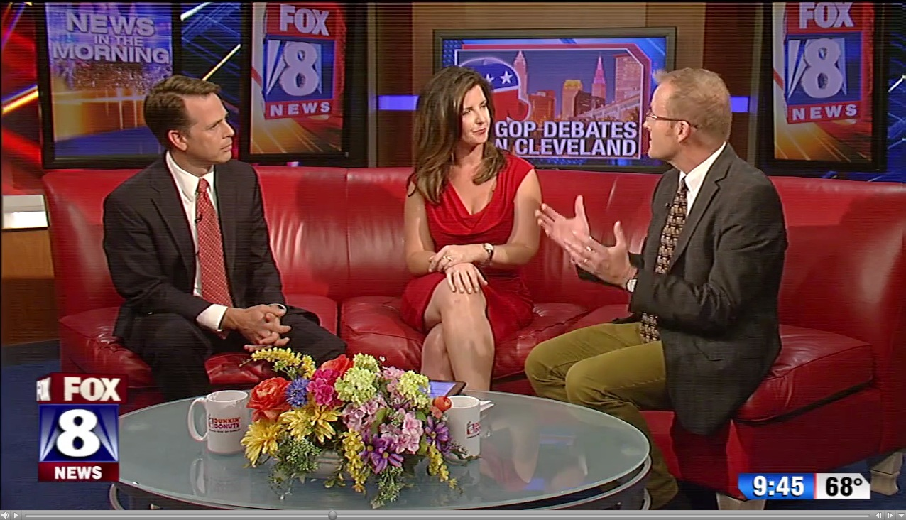 Image of Fox 8 Newsroom where Mark Cassell sits with two news anchors discussing '16 GOP candidates