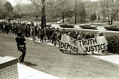 A demonstration is led with a banner reading 'The truth demands justice'