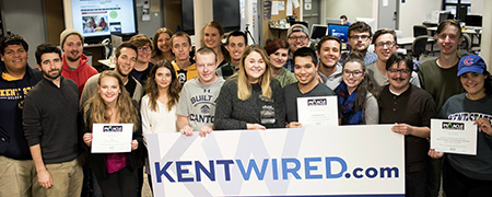 Members of Kent State University Student Media smile with their new awards in the newsroom in Franklin Hall.