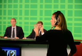 A TV2 floor director gives a signal to the on-air news team before the start of the 5:30 p.m. broadcast.