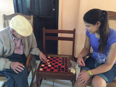 Paris Yanno using a game of checkers as therapy for an elder resident