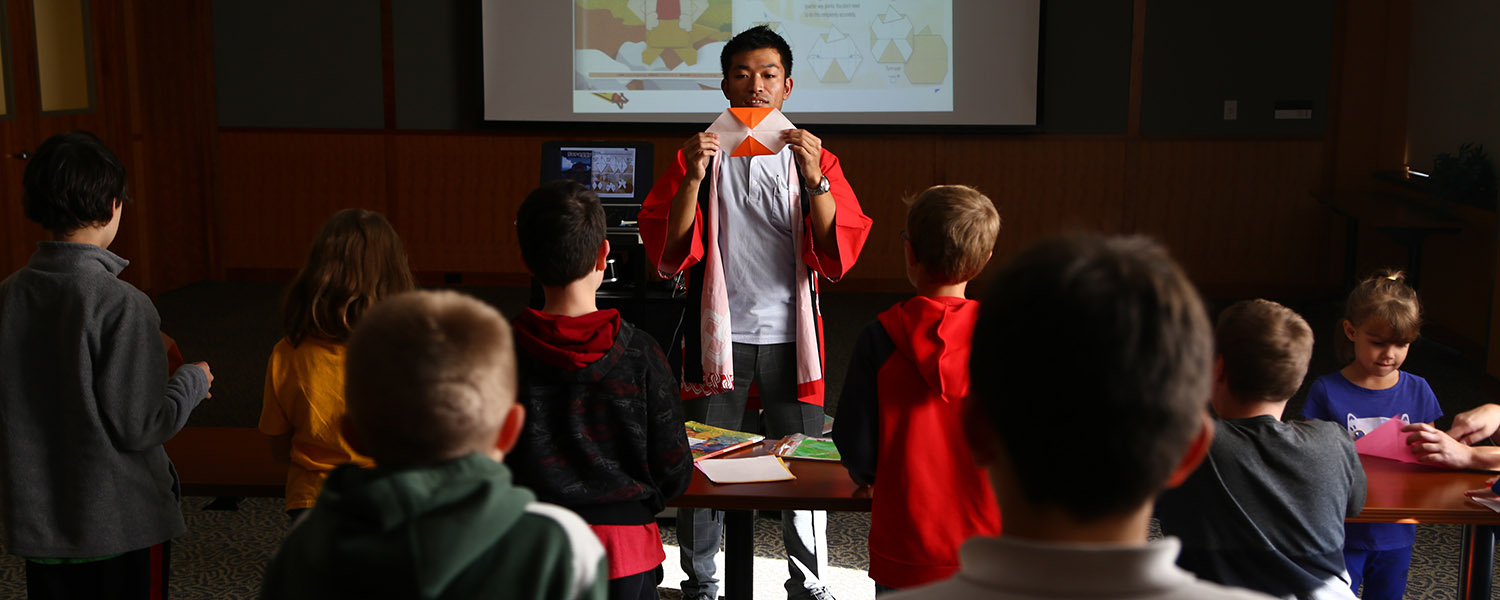 Haruhide Osugi, Kent State University's Japan Outreach Initiative coordinator, demonstrates origami to a group of students.