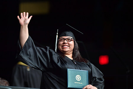A new Kent State University graduate waves to her family after receiving her diploma.