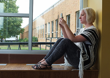 Student sitting in a window on their cellphone