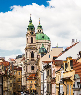 The iconic skyline of Prague is shown; there appears to be a large church in the background with a green roof.