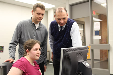 Joseph Kuvshinikov (right), associate professor at Kent State Ashtabula, meets with students from his capstone course Business Consulting and Practicum, which provides experience in providing consultation to a local client.