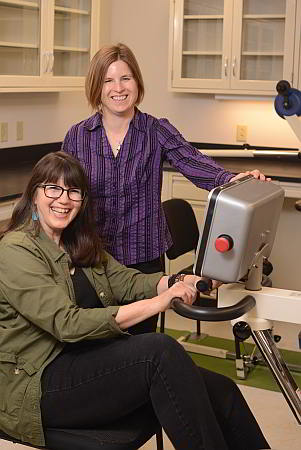 Kent State Associate Professor Angela Ridgel (standing) works with a Parkinson's patient on a specially designed treatment bike.