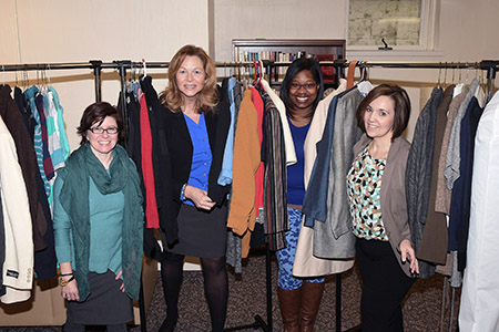 Tabitha Martin, Lori Bodnar, Alicia Robinson and Kristin Williams stand in the clothes racks at the Kent State Career Closet in the lower level of the Williamson House.