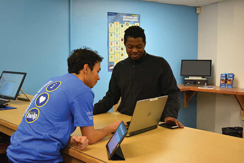 Service and Repair Center student employee helps a customer with their laptop at the counter