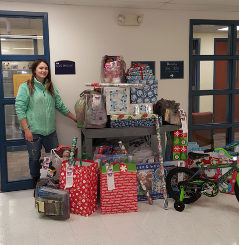 Shown with gifts collected by the SNA is Melissa Cave, treasurer.