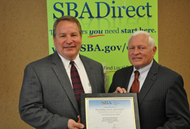 Steve Schillig (left) receives the 2013 Small Business Development Center Excellence and Innovation Award from Gil Goldberg (right), district director of the U.S. Small Business Administrations' Cleveland District office.