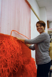 Graduate student Lisa Arenstein works on a tapestry loom that she constructed to create a large textural weaving.The Textile Art Studio will hold an open house on March 1.