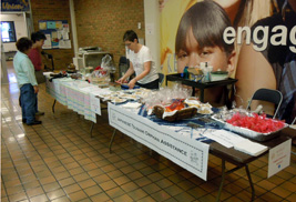 Volunteers prepare a table featuring authentic Japanese foods and items for sale during a fundraiser at Kent State University at Trumbull to benefit the Japanese Tsunami Orphan Assistance program.