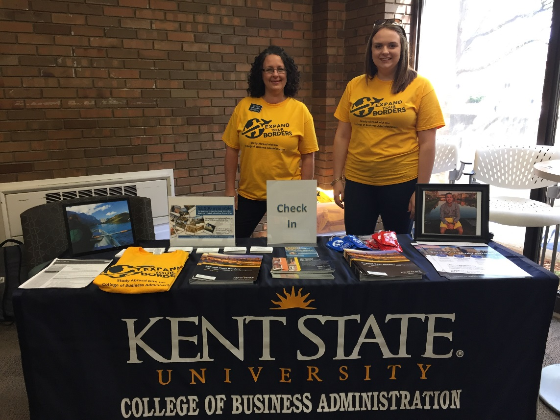 """Administrative Clerk Diane Sommers and student worker/study abroad alum Kaitlynn Dunn distributed t-shirts to those who completed the """"passport"""" activity at the 1st floor BSA check-in table."""