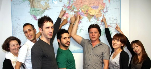 People Pointing at Various Places on a World Map
