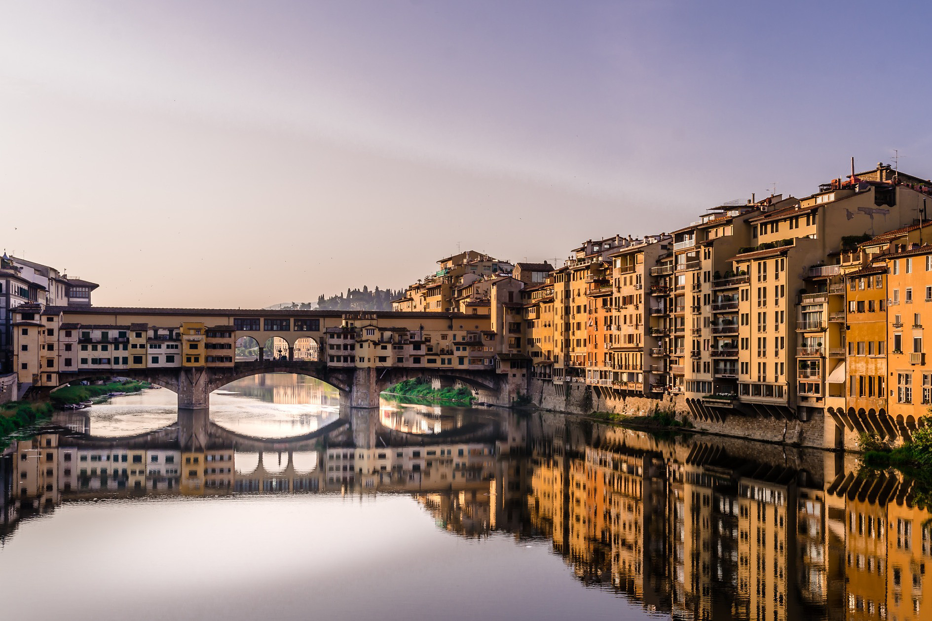 The sun sets over a bridge in Florence, Italy.