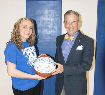 Chelsea Reynolds (left), a freshman at East Liverpool High School, is presented with the game ball by Dr. Steve Nameth, dean of the Kent State Columbiana County Campuses.