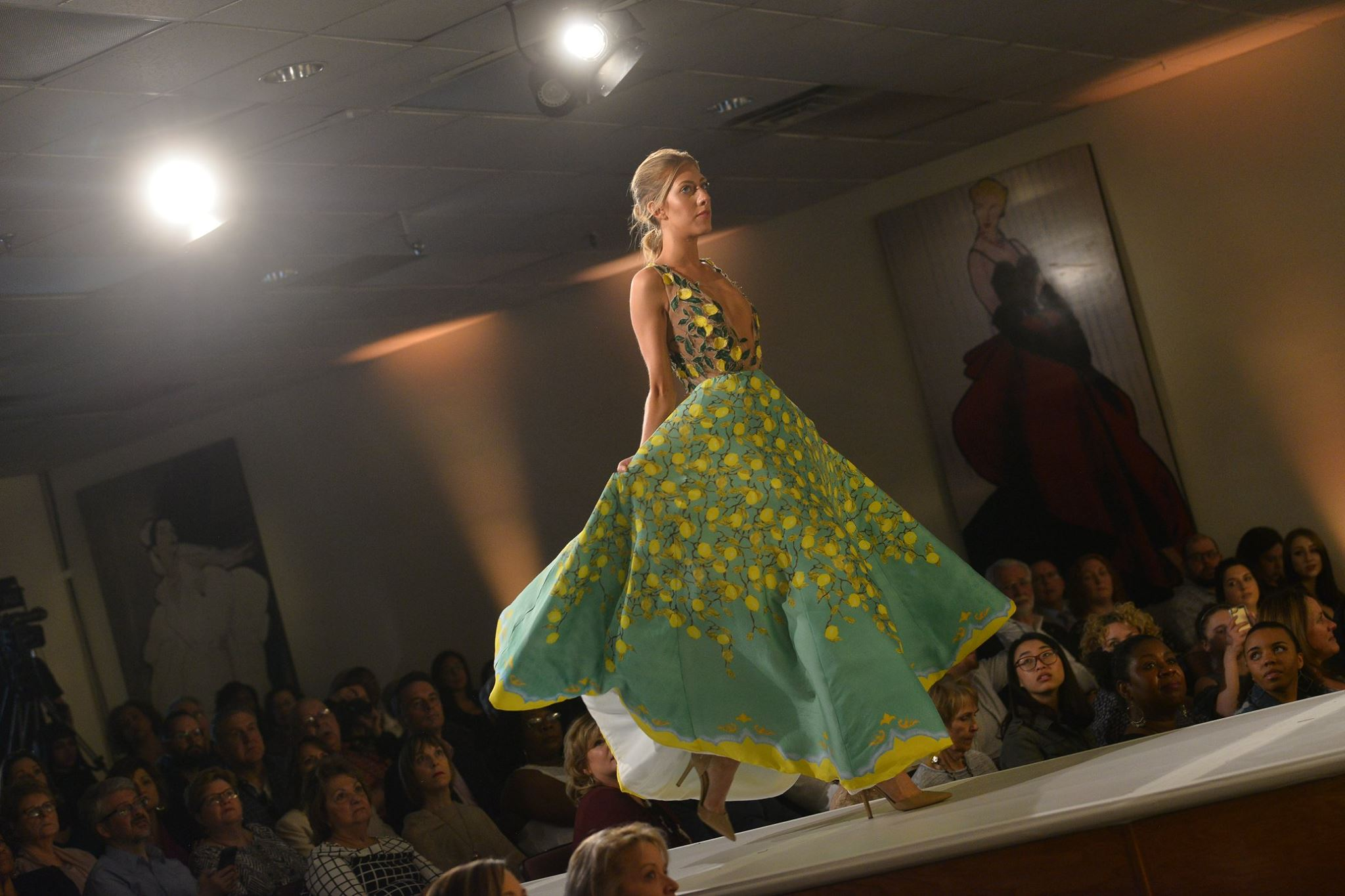 Model on runway sporting green and yellow gown during 2018 Fashion Show