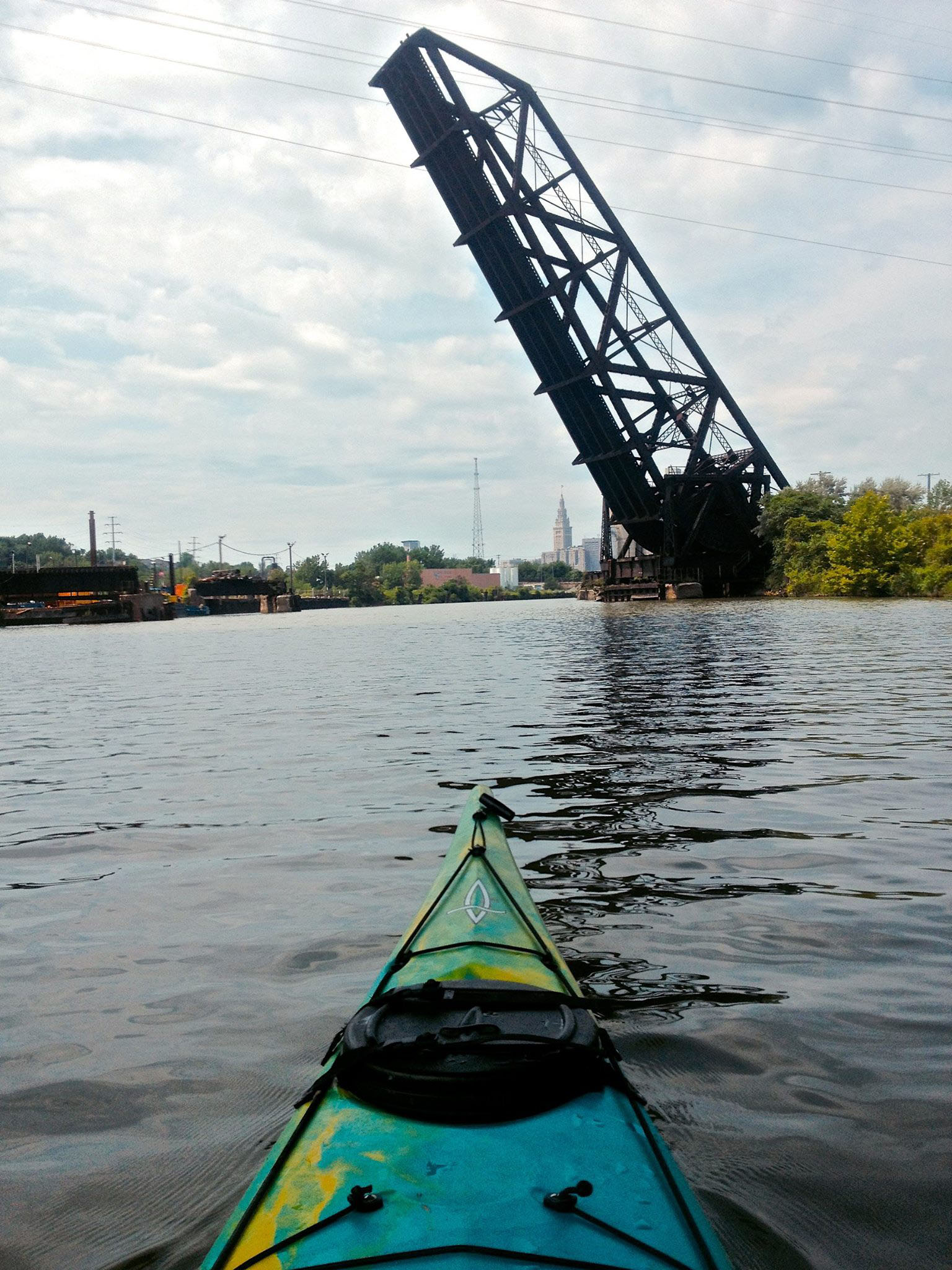 Entering the almost six-mile federal shipping channel through Cleveland, the river's current slows and huge smokestacks, freighters and slanted jackknife bridges loom on the horizon.