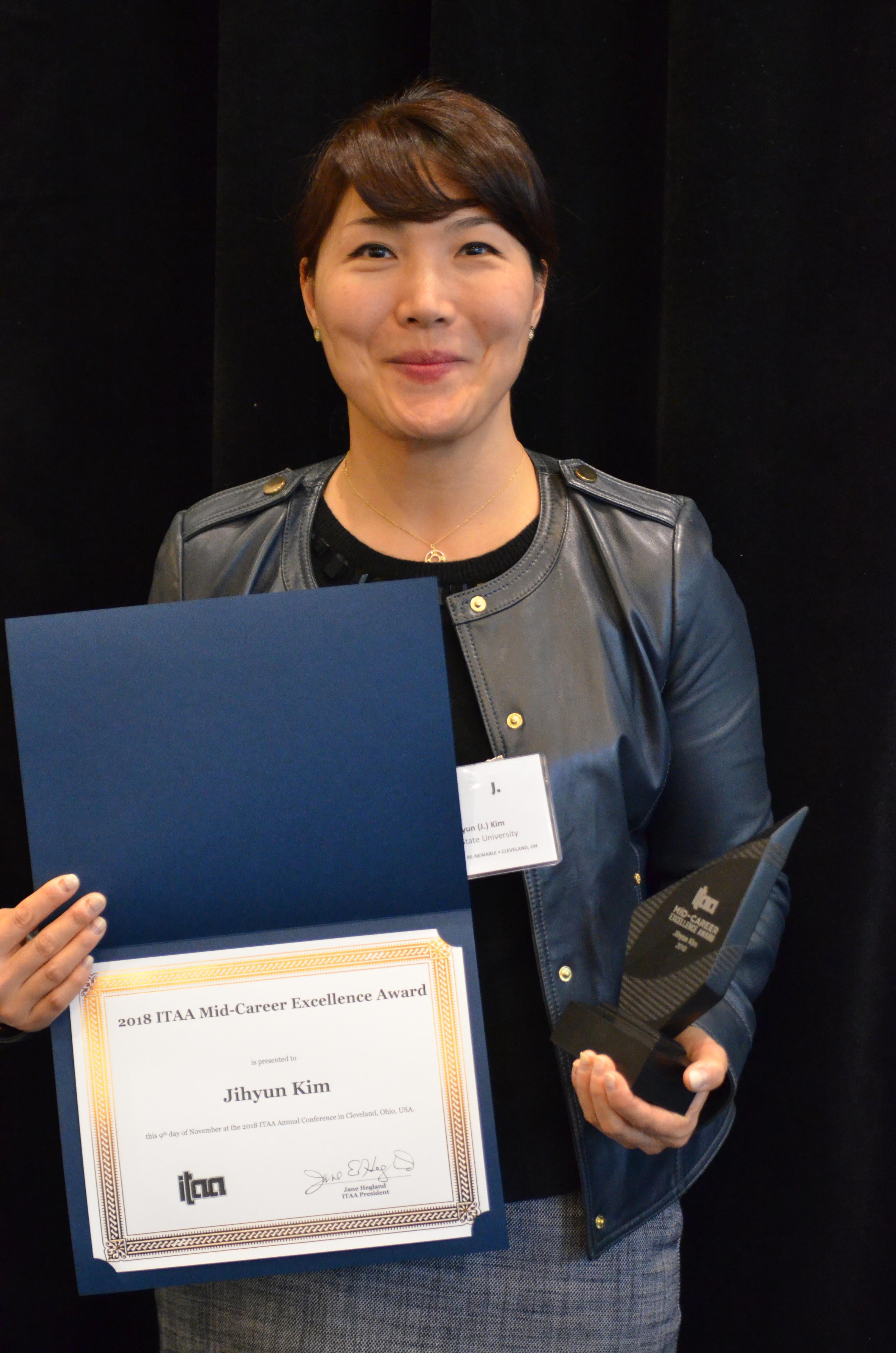 Dr. Jihyun Kim posing with award at the 2018 ITAA Awards in Cleveland.