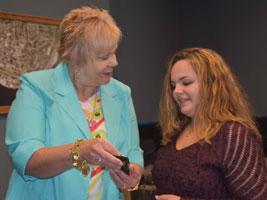 "Dr. Cristina Riter (left), program director, presents Alyssa Harris with a ""key to success"" key ring."