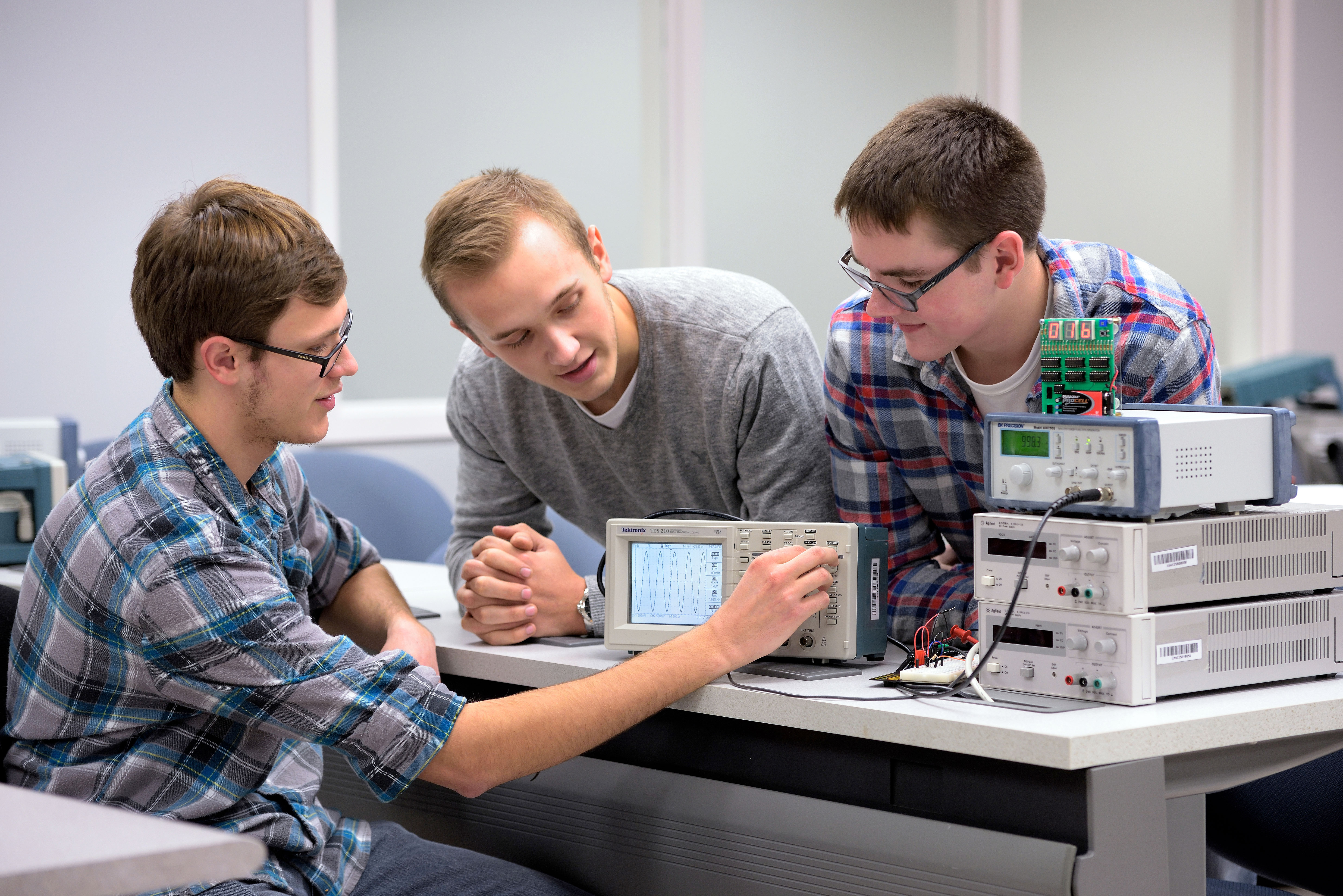 Electrical electronic students looking at a waveform on a digital oscilloscope