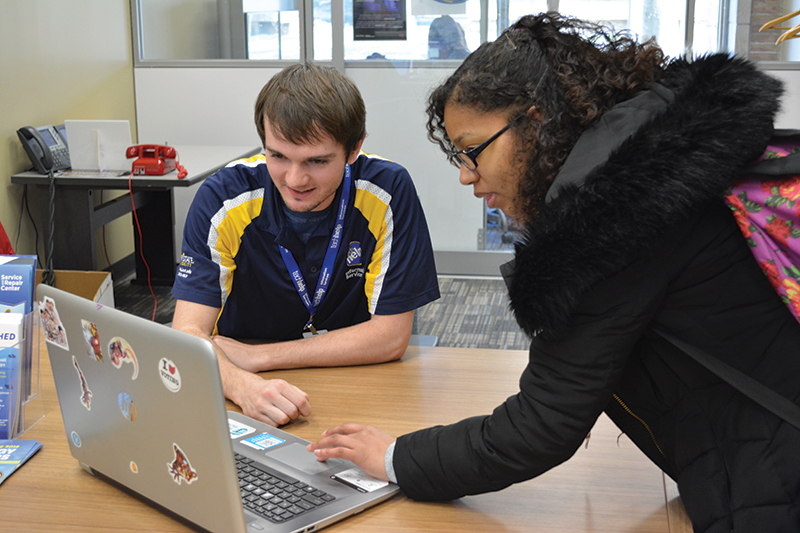 female student gets assistance at the library technology helpdesk