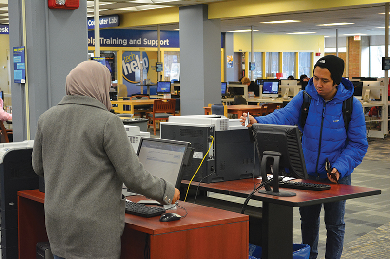two students using printer stations in the library
