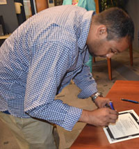 Mohamed AbouAmra signs his certificate and nursing pledge.