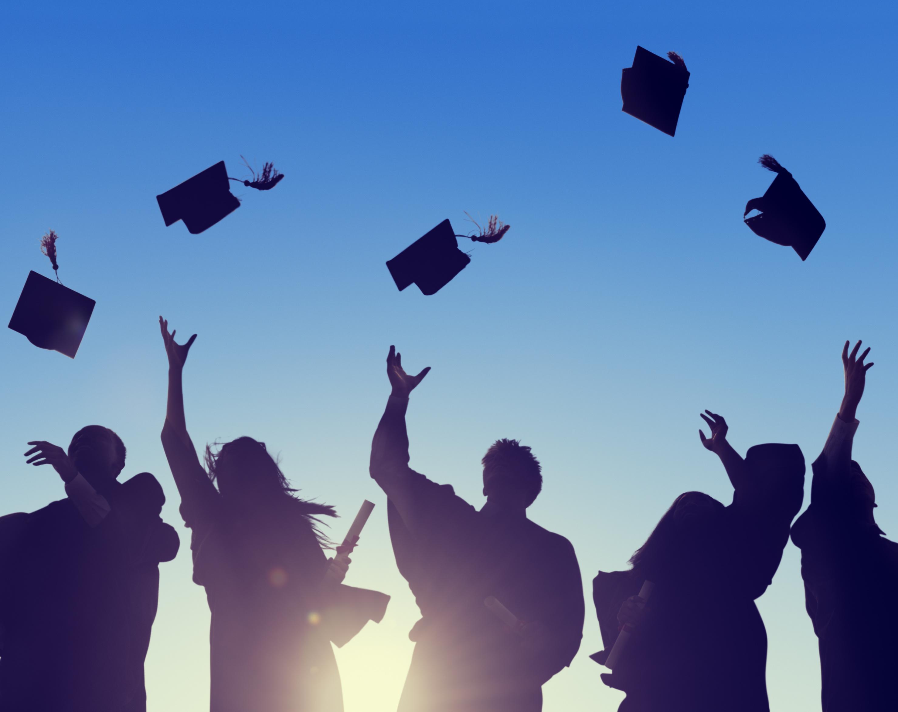 Student tossing graduation caps