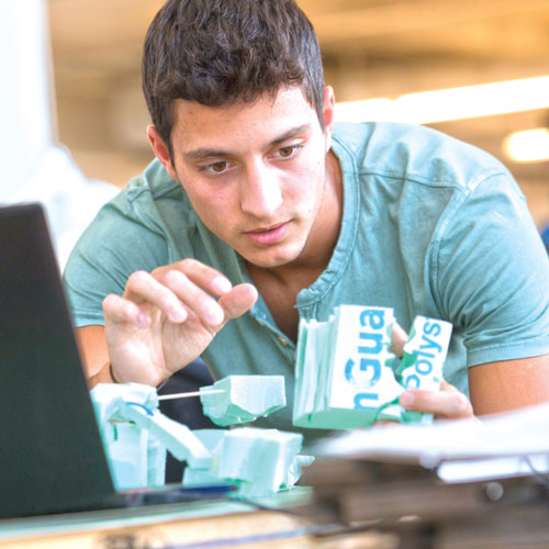 A student studies at a desk with a foam model