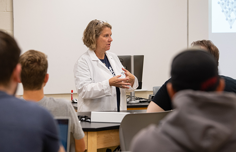 Professor teaching to students in front of classroom