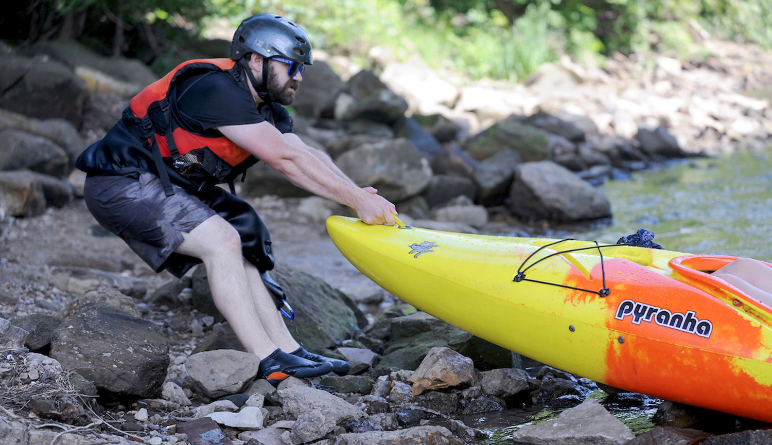 A Kent State University student pulls a kayak up on the bank of the Cuyahoga River.