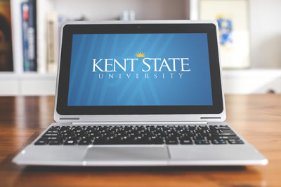 A laptop sitting on a desk near a bookshelf with the Kent State University logo overlayed on the screen